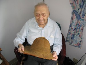 Major Barre pictured circa 2003 holding  a pith helmet signed by his uncle, Major Hercule Barre, in 1914.