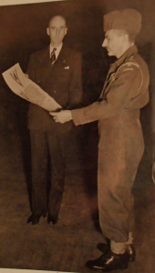 LCol (ret'd) Slessor presenting a scroll to LCol Brewer (wearing battle dress)