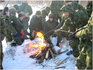 Members of The Royal Montreal Regiment cooking sausages over an open-air fire at the end of exercise Lynx Polaire in CFB Farnham early January 2016. Photo: Capt M.J. Szostak, RMR UPAR.