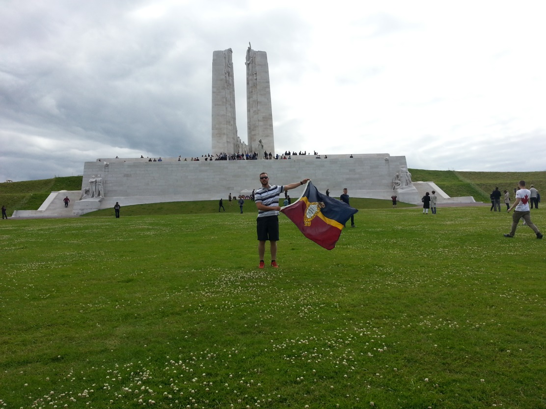 Corporal Duma with the RMR camp flag displayed in front of the Canadian national Vimy monument